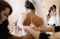 Happy stylish gorgeous blonde bride with bridesmaids on the back. Beautiful bride and bridesmaids posing in room before wedding Stock Photography