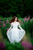 Beautiful bride in bright lace dress. In a field with Ivan-tea. Natural beauty, minimal makeup and loose hair.A child of Royalty Free Stock Image