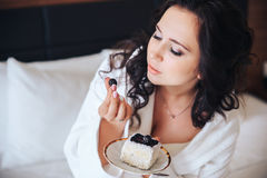 Beautiful bride brunette eat cake in a Bathrobe.  royalty free stock photography
