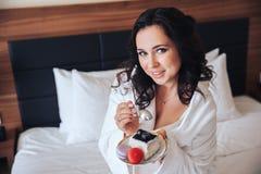Beautiful bride brunette eat cake in a Bathrobe.  stock image
