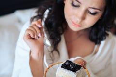 Beautiful bride brunette eat cake in a Bathrobe.  royalty free stock image