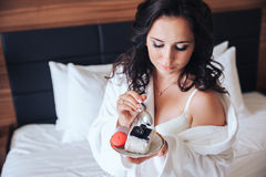 Beautiful bride brunette eat cake in a Bathrobe.  royalty free stock images