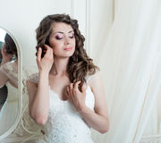 Beautiful bride brunette with  makeup. Beautiful bride brunette in white wedding dress with hairstyle and bright makeup Royalty Free Stock Photo