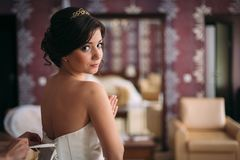 Beautiful bride brunette in a long wedding dress in a classic interior. Morning of the bride Stock Images