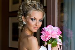Beautiful bride with bunch of flowers. Beautiful bride is standing at the window with bunch of flowers Stock Image