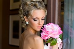 Beautiful bride with bunch of flowers. Beautiful bride is standing at the window with bunch of flowers Stock Images