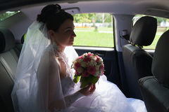 Beautiful bride in a car window Stock Photography