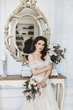 Beautiful bride, charming model brunette girl in stylish wedding lace dress with naked shoulders and wit a bouquet of flowers in h royalty free stock images