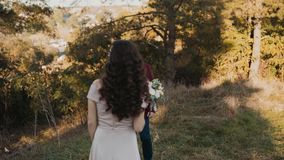 Beautiful bride comes to her lovely groom in golden park stock footage