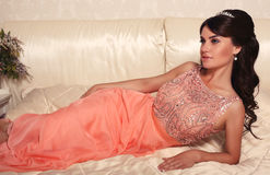 Beautiful bride with dark hair in elegant coral dress Stock Images