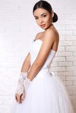 Beautiful bride with dark hair in elegant wedding dress with accessories Stock Photo