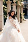 beautiful bride with dark hair in luxurious wedding dress in elegant villa stock photo