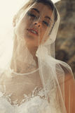 Beautiful bride with dark hair in luxurious wedding dress. Fashion outdoor photo of gorgeous bride with dark hair wears luxurious wedding dress, posing on royalty free stock photography