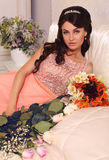 Beautiful bride with dark hair posing with bouquet of flowers Royalty Free Stock Photography