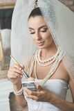 Beautiful bride doing makeup Royalty Free Stock Photography
