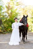 A beautiful bride in a dress leads behind a bridle horse. stock photo