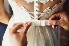 Beautiful bride dress. Witness tying a bow wedding dress on the bride stock image