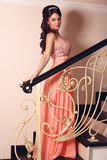 Beautiful bride in elegant coral dress posing on stairs Royalty Free Stock Image