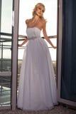 Beautiful bride in elegant dress posing at balcony Royalty Free Stock Images