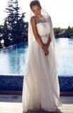 Beautiful bride in elegant dress posing beside s swimming pool Stock Images