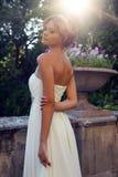 Beautiful bride in elegant dress posing in sunlight rays. Tender photo of beautiful bride in elegant dress posing at park in sunlight rays Royalty Free Stock Image
