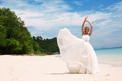 Beautiful bride in elegant wedding dress posing on beach in Thailand Royalty Free Stock Image