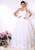 Beautiful bride in elegant wedding dress posing among flowers Stock Images