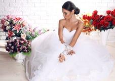 Beautiful bride in elegant wedding dress posing among flowers Stock Photography