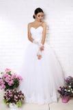 Beautiful bride in elegant wedding dress posing among flowers Stock Image