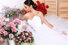 Beautiful bride in elegant wedding dress posing among flowers Royalty Free Stock Image