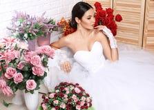 Beautiful bride in elegant wedding dress posing among flowers Royalty Free Stock Photos