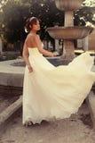Beautiful bride in elegant wedding dress posing at park Stock Image
