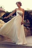 Beautiful bride in elegant wedding dress posing at summer park Royalty Free Stock Images