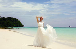 Beautiful bride in elegant wedding dress posing on tropical beach Royalty Free Stock Photo