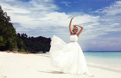 Beautiful bride in elegant wedding dress posing on tropical beach Royalty Free Stock Photography