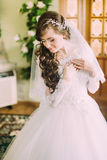 Beautiful bride in elegant white wedding dress and veil with long curly hair posing indoors Royalty Free Stock Images