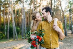 Beautiful bride embraces her groom by the shoulder. Wedding walk in a forest. A newlywed looks at each other. Girl in Royalty Free Stock Photos