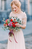Beautiful bride with eyes closed holds a huge bouquet of roses and peonies with ancient european architecture on Royalty Free Stock Photos