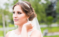 Beautiful bride with fashion earrings, outdoors portrait in park. Beautiful bride with long wavy hair and fashion earrings, posing in wedding dress, outdoors Royalty Free Stock Photo