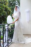 Beautiful bride in fashion wedding dress on natural background. The stunning young bride is incredibly happy. Wedding royalty free stock images