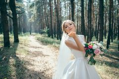A beautiful bride portrait in the forest. The stunning young bride is incredibly happy. Wedding day. Beautiful bride in fashion wedding dress on natural stock photos