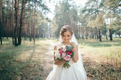A beautiful bride portrait in the forest. The stunning young bride is incredibly happy. Wedding day. Beautiful bride in fashion wedding dress on natural royalty free stock photos