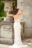 Beautiful bride in fashion wedding dress posing by roman flower Stock Photo