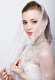 Beautiful bride with fashion wedding hairstyle. Close-up portrait of young gorgeous bride. Wedding. girl covers her face Stock Images