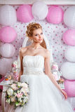 Beautiful bride with fashion wedding hairstyle and wedding dress posing in studio Stock Photography