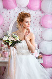 Beautiful bride with fashion wedding hairstyle and wedding dress posing in studio Royalty Free Stock Photos