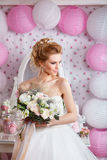Beautiful bride with fashion wedding hairstyle and wedding dress posing in studio Stock Photos