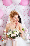 Beautiful bride with fashion wedding hairstyle and wedding dress posing in studio Royalty Free Stock Photography