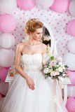 Beautiful bride with fashion wedding hairstyle and wedding dress posing in studio Royalty Free Stock Photo