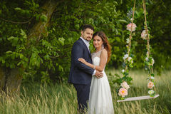 Beautiful bride with fiance is swinging on a swing Stock Photography
